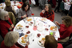 Guests enjoying Fudge Cheesecake with Cherry Sauce