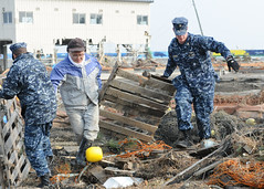MISAWA, Japan (March 14, 2011) Chief Naval Air Crewmen Kyle Wilkinson, sssigned to Naval Air Facility Misawa (NAFM), assists in removing debris during a cleanup effort at the Misawa Fishing Port. (U.S. Navy photo by Mass Communication Specialist 2nd Class Devon Dow)
