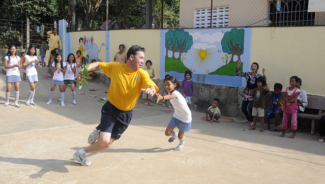 Sailor plays tag with a Cambodian child by CC user usnavy on Flickr