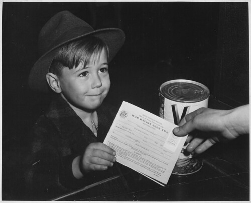 An eager school boy gets his first experience in using War Ration Book Two