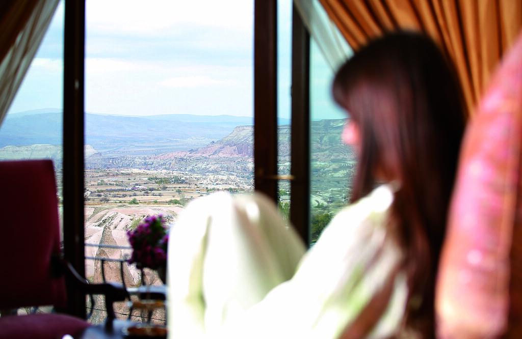 カッパドキアの風景をCAVE RESORT AND SPAの部屋の中から見下ろす女性
