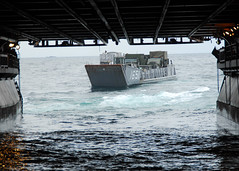 In this March 26, file photo, landing craft utility 1651 debarks the well deck of the forward-deployed amphibious assault ship USS Essex (LHD 2) to transfer humanitarian assistance and disaster relief supplies to USS Harpers Ferry (LSD 49). On March 27, LCUs were used to transfer needed equipment to Oshima Island to restore power that had been lost since the March 11 earthquake and tsunami. (U.S. Navy photo by Mass Communication Specialist 2nd Class Eva-Marie Ramsaran)