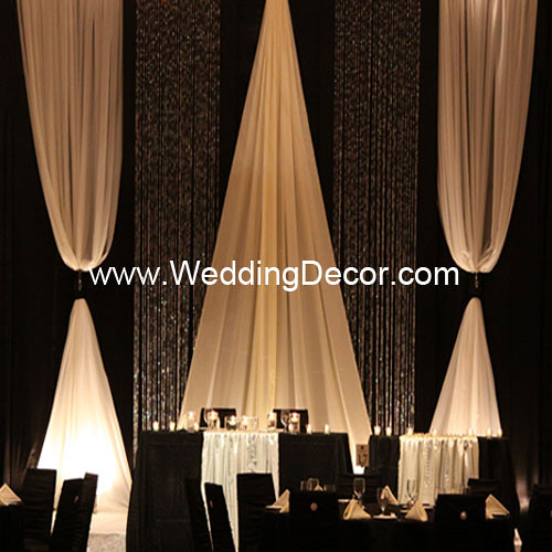 A black and ivory wedding backdrop with matching head table and cake table