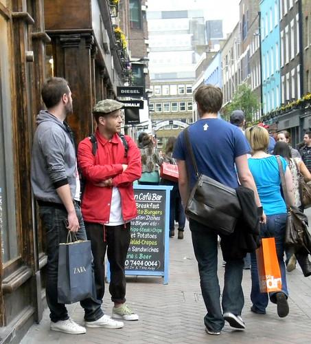 Two men talking cap Carnaby Street soho London 2nd April 2011 16:36.58pm