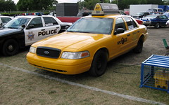 police(0.0), taxi(1.0), automobile(1.0), automotive exterior(1.0), ford crown victoria police interceptor(1.0), vehicle(1.0), police car(1.0), compact car(1.0), ford(1.0), ford crown victoria(1.0), land vehicle(1.0), luxury vehicle(1.0), motor vehicle(1.0),