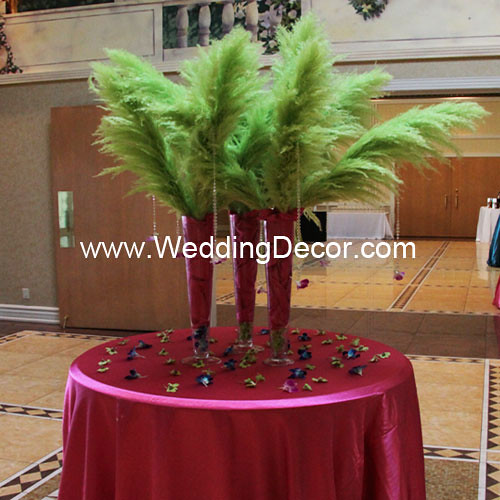 Masquerade wedding themed reception with green feather arrangements in