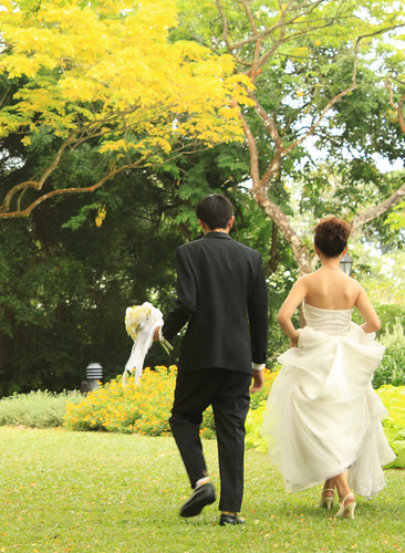 A bride and groom running through a park in the summer