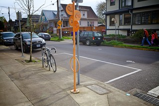 Car share parking space with iconic sign post that doubles as bike parking.