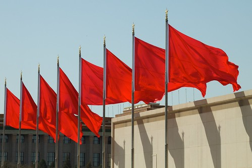 Line of eight red flags blowing in the air.
