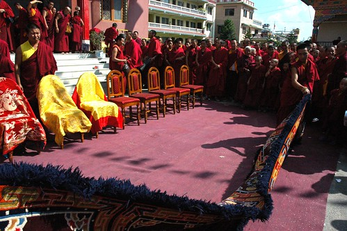 Monks begin to roll out Tibetan carpets and silk chair covers over wood chairs for the senior Sakya Lamas, Sakya Lamdre, Tharlam Monastery Courtyard, Tibetan Buddhism, many monks and nuns, Boudha, Kathmandu, Nepal by Wonderlane