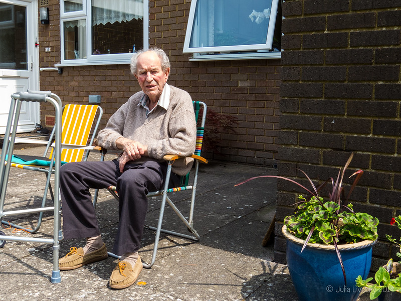 Dad sits outside the flat in the sun