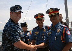 PUERTA PRINCESA, Republic of the Philippines (June 27, 2011) - Lt. Cmdr. Kenneth Brown, Commanding Officer USS Guardian (MCM 5), presents a photo of Guardian and a ship's coin to Police Senior Superintendent Virgilio C. Parrocha, City Director of the Puerto Princesa City Police, after a pier-side tour of the ship. (U.S. Navy Photo by Lt. Colby Drake)