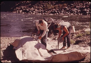 Members of wilderness expedition inflate a 28-foot raft at the beginning of a trip through Hells Canyon on the Snake River, 05/1973
