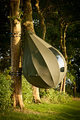 """In the landscape, next to the lane heading to the castle of Hex, you can find four tree tents where you can spend the night. The tear-shaped sculptures are hanging from standard trees and provide an alternative form of accommodation to spend a night in Haspengouw. The work of Dré Wapenaar (NL) is always situated on the border between architecture and sculpture, between a stay and a meet. His sculptures are mainly tent constructions that are placed temporarily. The social interaction around the work is of great importance for the artist.  At the tree tents of Dré Wapenaar in Tradendreef you can now also find Field Furniture """"Pure Nature"""" by Ardie Van Bommel (NL). She brings a sit, wash, toilet and barbecue unit based on the palettes or fruit chests that you can often see in the Haspengouw landscape.  Would you like to spend the night in a tree tent by Dré Wapenaar? Overnight stay from March 21st until September 30th, 2012. You can camp in a tree tent with two adults and possibly two small children. Book now an alternative night in Haspengouw!  Practical info  On display / overnight stay possible: . March 21st –September 30th, 2012  Info and bookings: . Tourism Borgloon – Markt z/n, Borgloon – 012 67 36 53 . Price: € 70 per night; € 30 per breakfast per tent (optional)  Location: . Lane headed to the Castle of Hex (side street of Alfonsstraat), Bommershoven (Borgloon)  Access: . limited parking facilities – beware of getting your car stuck due to wet surfaces  www.z33.be/en/z-out/pit/dre-wapenaar-tranendreef  part of pit - art in the public space of Borgloon-Heers 