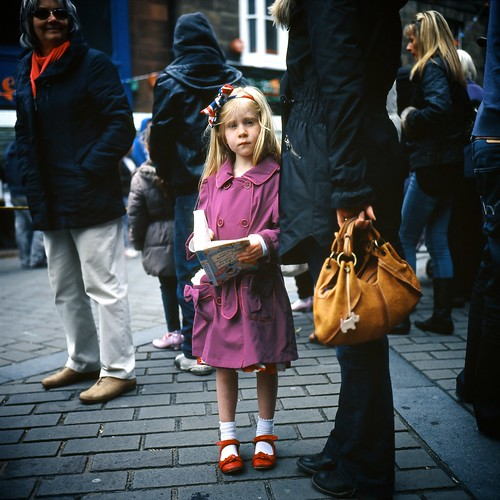 Girl with red shoes at parade.