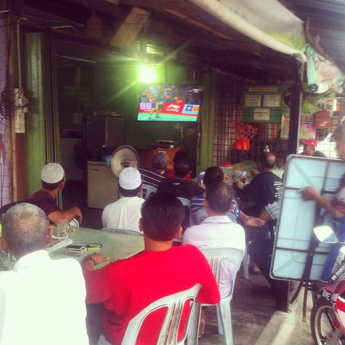 Villagers gather catch the finals of the 2014 Thomas Cup.