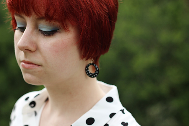 short red hair, blue eye shadow, and polka dot earrings