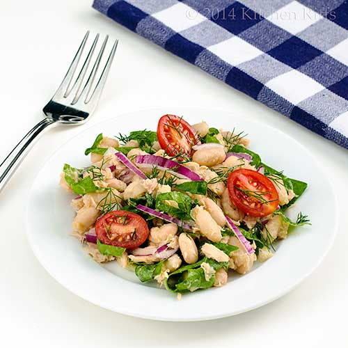 White Bean, Tuna, and Swiss Chard Salad with cherry tomato garnish