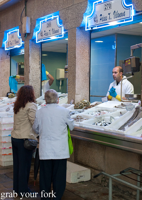 Seafood stall and shoppers at Mercado de Abastos farmers market in Santiago de Compostela, Spain