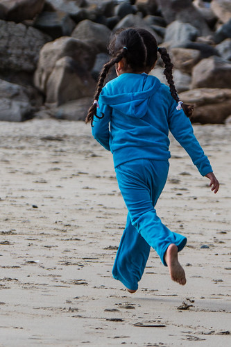 Cute little girl with pigtails in blue outfit romps and jumps on the sand beach.