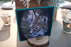 Escort card with Eurasian lynx photo displayed on dinner table at wedding