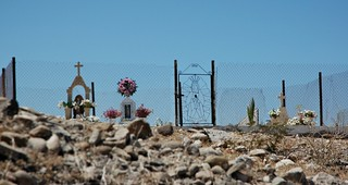Our Lady of Guadalupe, headstones, roses and flowers, daisies, fencing, Hillside Cemetery, stones, San Rosalia, Baja California Sur, Mexico