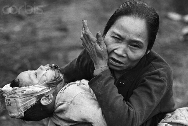 With a wounded baby in her arms, an elderly Vietnamese woman makes a plea for help as she arrives at a U.S. Marine aid station, Hue, Vietnam, by Kyoichi Sawada 1968
