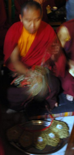 A Tibetan Buddhist monk placing ritual diety crowns on the silver tray, Sakya Lamdre, Tharlam Monastery of Tibetan Buddhism, Boudha, Kathmandu, Nepal by Wonderlane