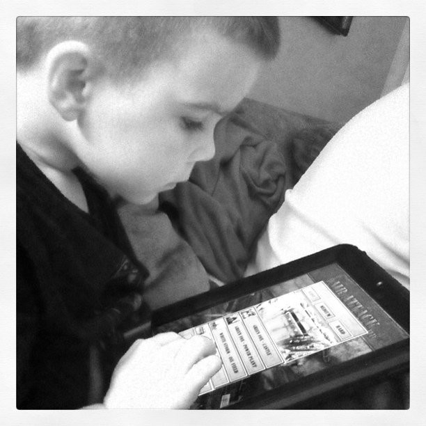 He is flying planes on the iPad.