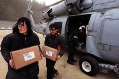 NORTHERN JAPAN (March 15, 2011) Japanese citizens move food and water out of an HH-60H Sea Hawk helicopter assigned to the Black Knights of Helicopter Anti-Submarine Squadron (HS) 4. (U.S. Navy photo by Mass Communication Specialist 3rd Class Alexander Tidd)