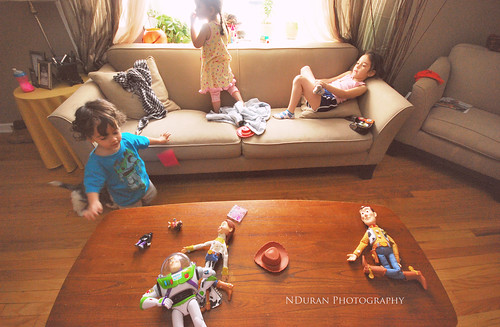 Several children play on a couch and around a coffee table