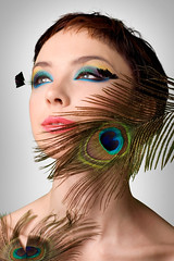 clothing(0.0), human body(0.0), blond(0.0), nose(1.0), face(1.0), feather(1.0), model(1.0), skin(1.0), head(1.0), hair(1.0), eyelash(1.0), green(1.0), fashion(1.0), photo shoot(1.0), close-up(1.0), illustration(1.0), blue(1.0), beauty(1.0), portrait(1.0), eye(1.0), organ(1.0),