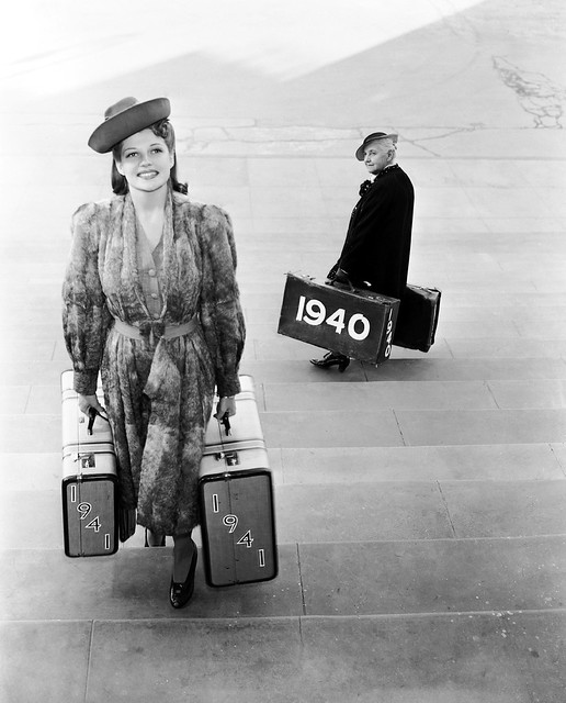 1941: A young Rita Hayworth (1918 - 1987) sees in the New Year with a pair of '1941' suitcases as she passes someone carrying a pair of '1940' suitcases on the way down.
