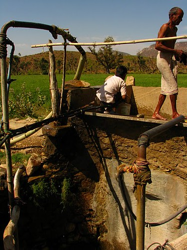 Two men set up irrigation at their well