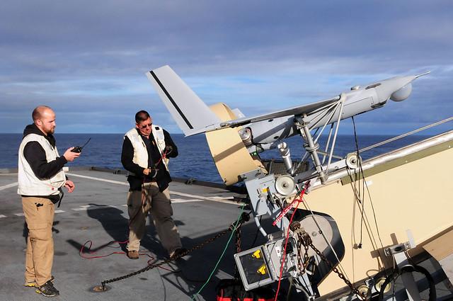 Τεχνικό προσωπικό των εταιρειών Boeing και Insitu Group πραγματοποιούν ελέγχους πριν την πρώτη πτήση του μη επανδρωμένου αεροπλάνου Scan Eagle από το αποβατικό σκάφος USS Comstock (LSD 45). (Φωτογραφία: US Navy)