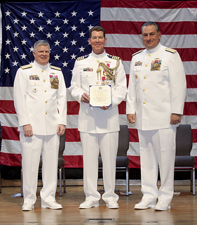 Capt. John Bingaman, Coast Guard 9th District chief of staff, displays his certificate of retirement, presented to him by Rear Adm. Fred Midgette to his left and retired Rear Adm. Michael Parks to his right. Bingaman retired after 30 years of military service at a ceremony held at Bay Village Presbyterian Church, Friday. (U.S. Coast Guard photo by Coast Guard Auxiliarist Mark Galan)
