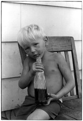 Young boy (age three or four) holding pepsi bottle, sitting on chair outdoors, Kentucky, 1971, by William Gedney