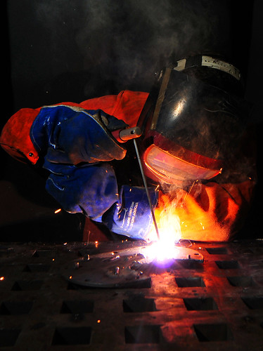 Sailor arc-welds a flange aboard amphibious dock landing ship.
