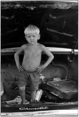 Small shirtless boy standing in trunk of car with hands on hips, Kentucky 1971, by William Gedney
