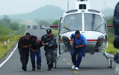 Police take a suspected drug trafficker off a helicopter