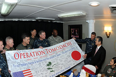 Navy Adm. Patrick M. Walsh, commander of U.S. Pacific Fleet, center, joins other senior U.S. military members supporting Operation Tomodachi in presenting Japanese Defense Minister Toshimi Kitazawa with a banner as he and senior Japanese leaders visit the aircraft carrier USS Ronald Reagan, April 4, 2011. Walsh credits the U.S. forward presence in the region with providing a rapid response -- whether for humanitarian assistance or to deter aggression. (U.S. Navy photo by Petty Officer 3rd Class Kyle Carlstrom)