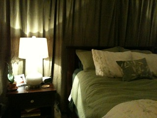 Bedroom nightstand. I live the white lamp and orchid against the green curtain!