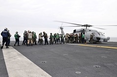 PACIFIC OCEAN (March 19, 2011) Sailors and Marines aboard the aircraft carrier USS Ronald Reagan (CVN 76) load humanitarian assistance supplies onto an HH-60H Sea Hawk helicopter assigned to the Black Knights of Anti-Submarine Squadron (HS) 4. Ronald Reagan is operating off the coast of Japan providing humanitarian assistance as directed in support of Operation Tomodachi. (U.S. Navy photo by Mass Communication Specialist Seaman Nicholas A. Groesch)