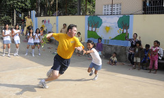 SIHANOUKVILLE, Cambodia (March 1, 2011) Chief Operations Specialist Steven Rowlands avoids a girl's tag during a game of nap lungdy during a Commander, Amphibious Squadron 11 community service project at the Goodwill School. (U.S. Navy photo by Mass Communications Specialist 1st Class Johnie Hickmon)