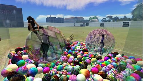 Several people stand inside of a nearly clear box filled with a wide variety of textured balls, most of them variations on rainbows. Two of the people are inside larger balls, and one of the three is sitting on top of one of the larger balls.