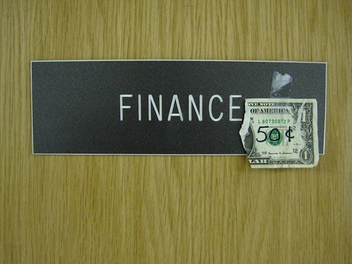 "Sign that says finance with half a dollar bill stuck to it and ""50c"" written on the bill"