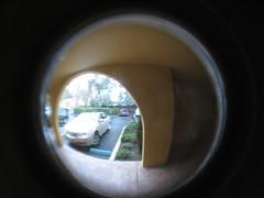 porthole(0.0), glass(0.0), reflection(0.0), eye(0.0), organ(0.0), window(1.0), yellow(1.0), white(1.0), photograph(1.0), light(1.0), fisheye lens(1.0), close-up(1.0), circle(1.0),