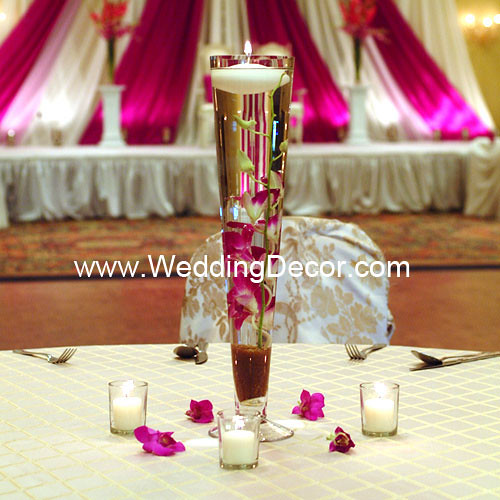 A wedding centerpieces with gold crushed glass fuchsia orchid stems and