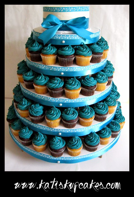 A wedding cupcake tower with a matching small cutting cake in colors of teal