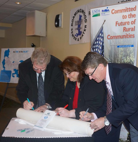 Tom Williams, PA RD State Director, Jacki Ponti-Lazaruk, RD WEP Program Assistant Administrator, and Jack Lennox, Roamingwood Water & Sewer Association General Manager, ceremoniously sign a portion of the new pipe that will replace old lines in the current system, making the system more energy, cost and water efficient.